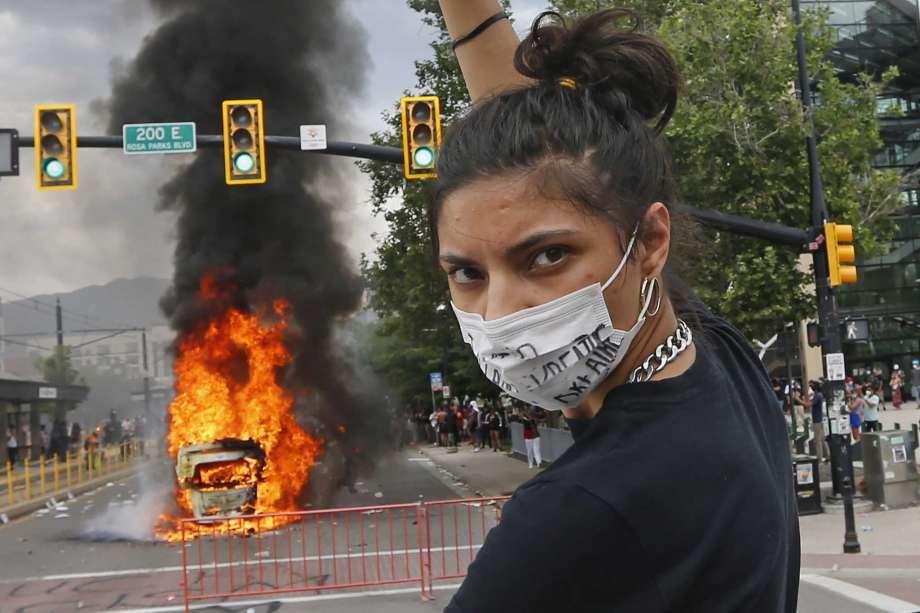 متظاهرة بجانب سيارة محترقة