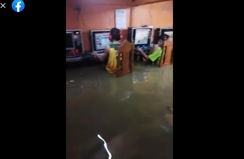 أطفال يلعبون في مقهى إنترنت خلال فيضانات الصين مضلل فتبينوا